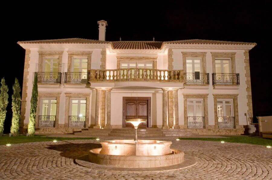 Fachada Exterior de villa decorada de travertino en ventanas cornisas y balaustradas